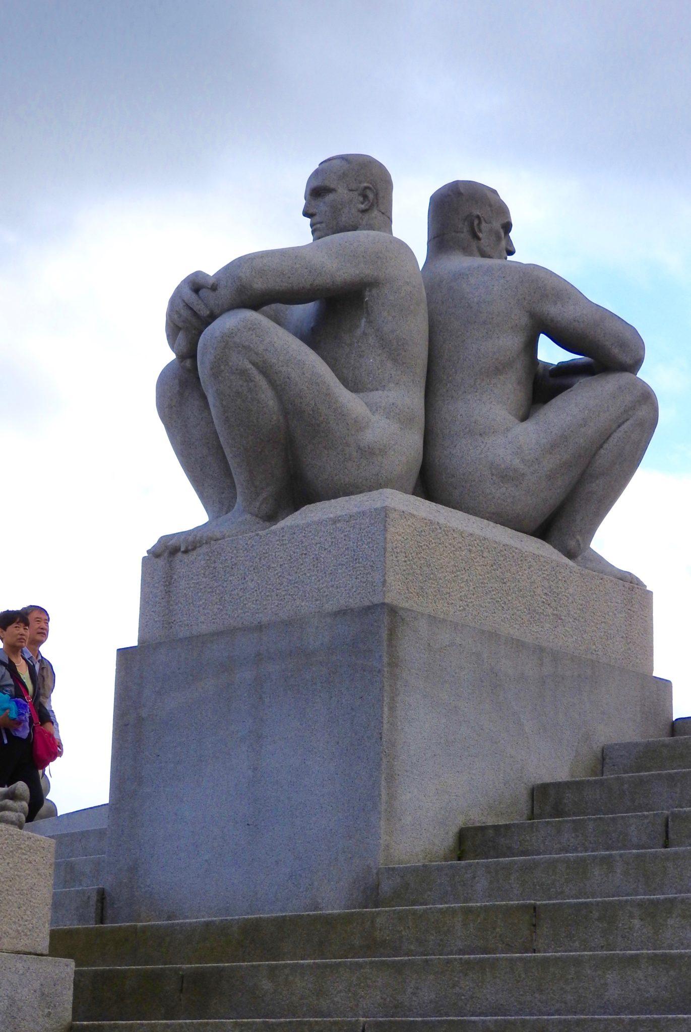 Granite statues of men sitting back to back