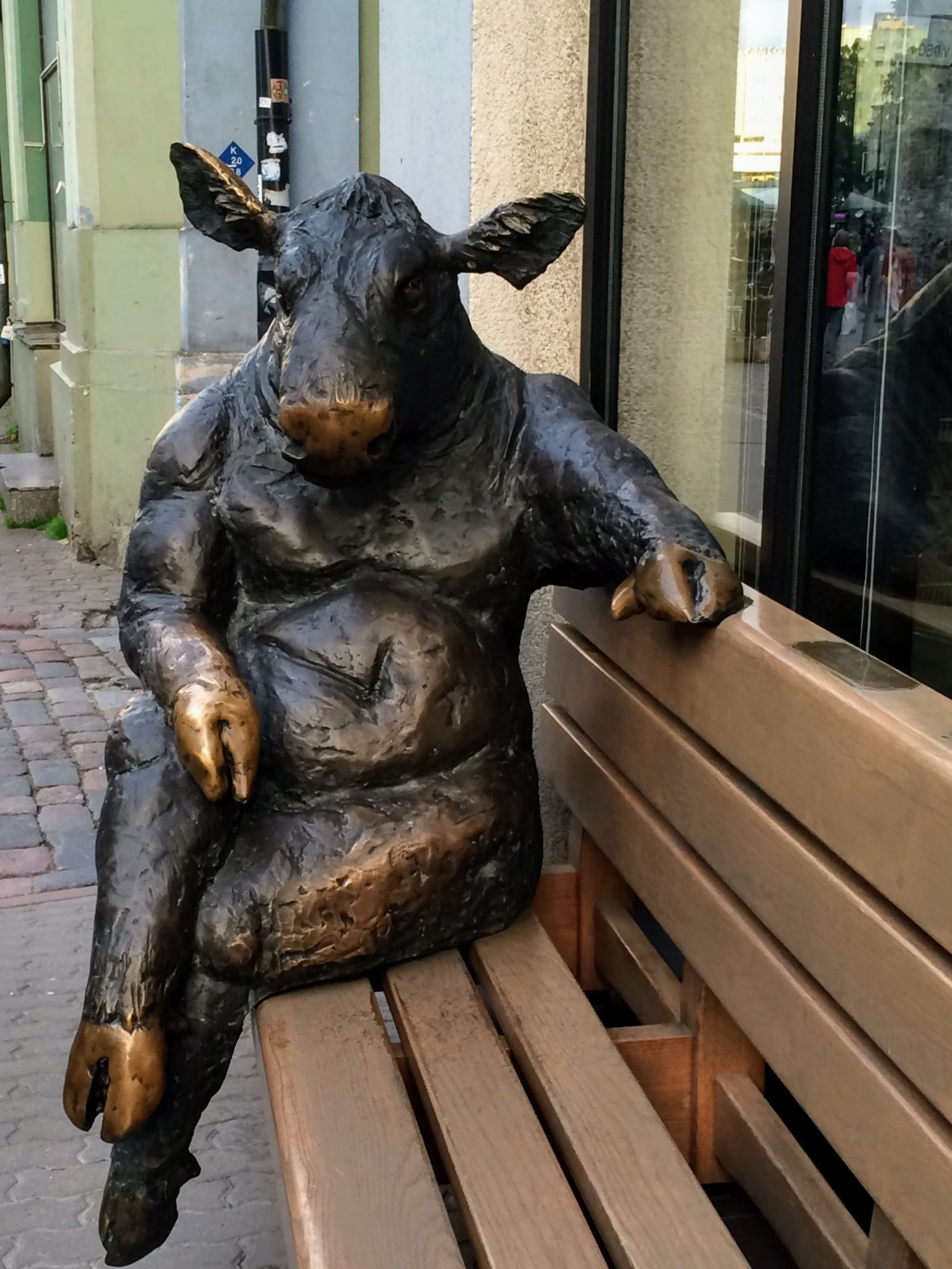 Bronze statue of a cow seated on a bench Tallinn, Estonia