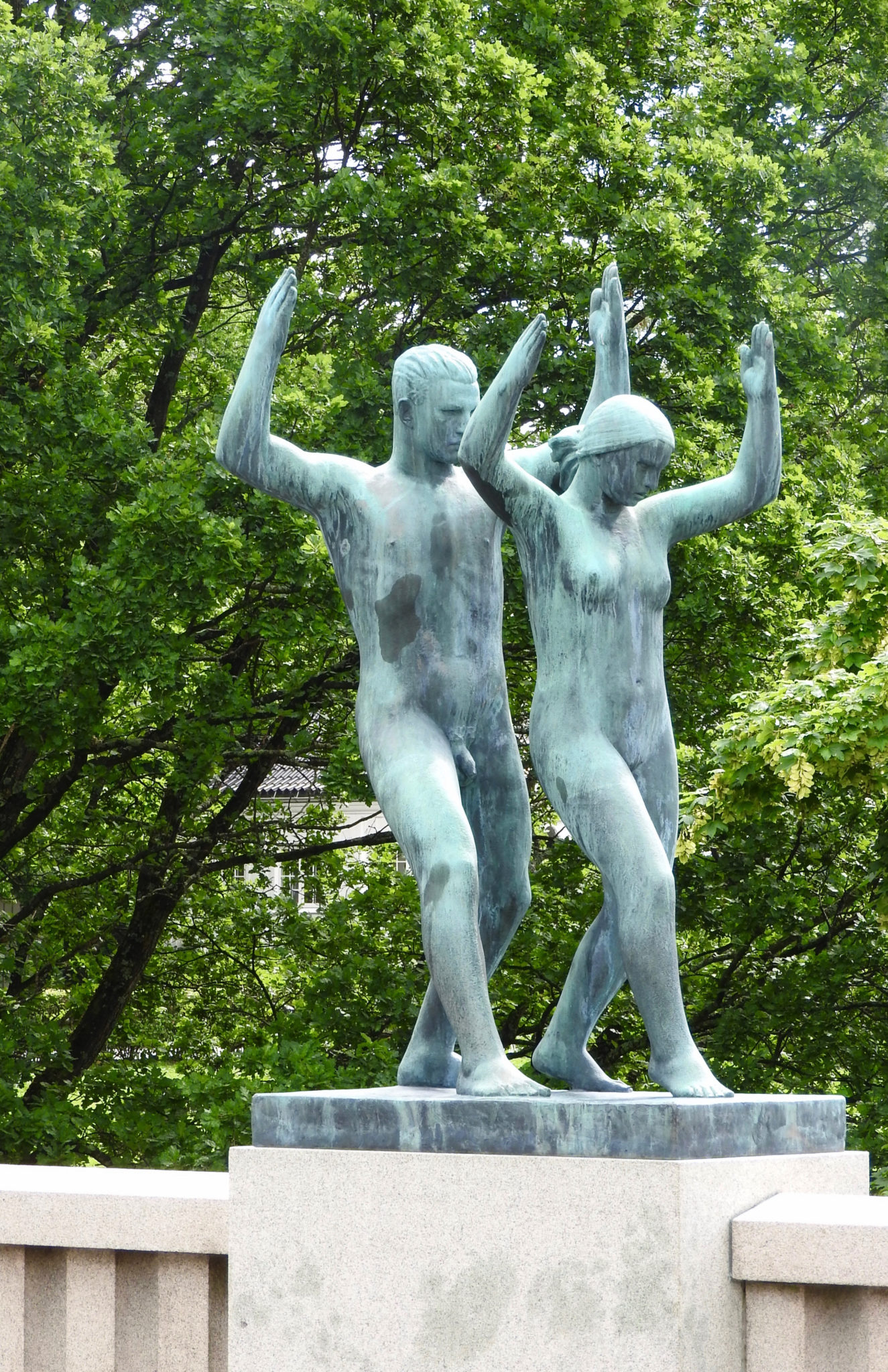 Matching sculptures of a young man and woman standing with knees bent and arms raised
