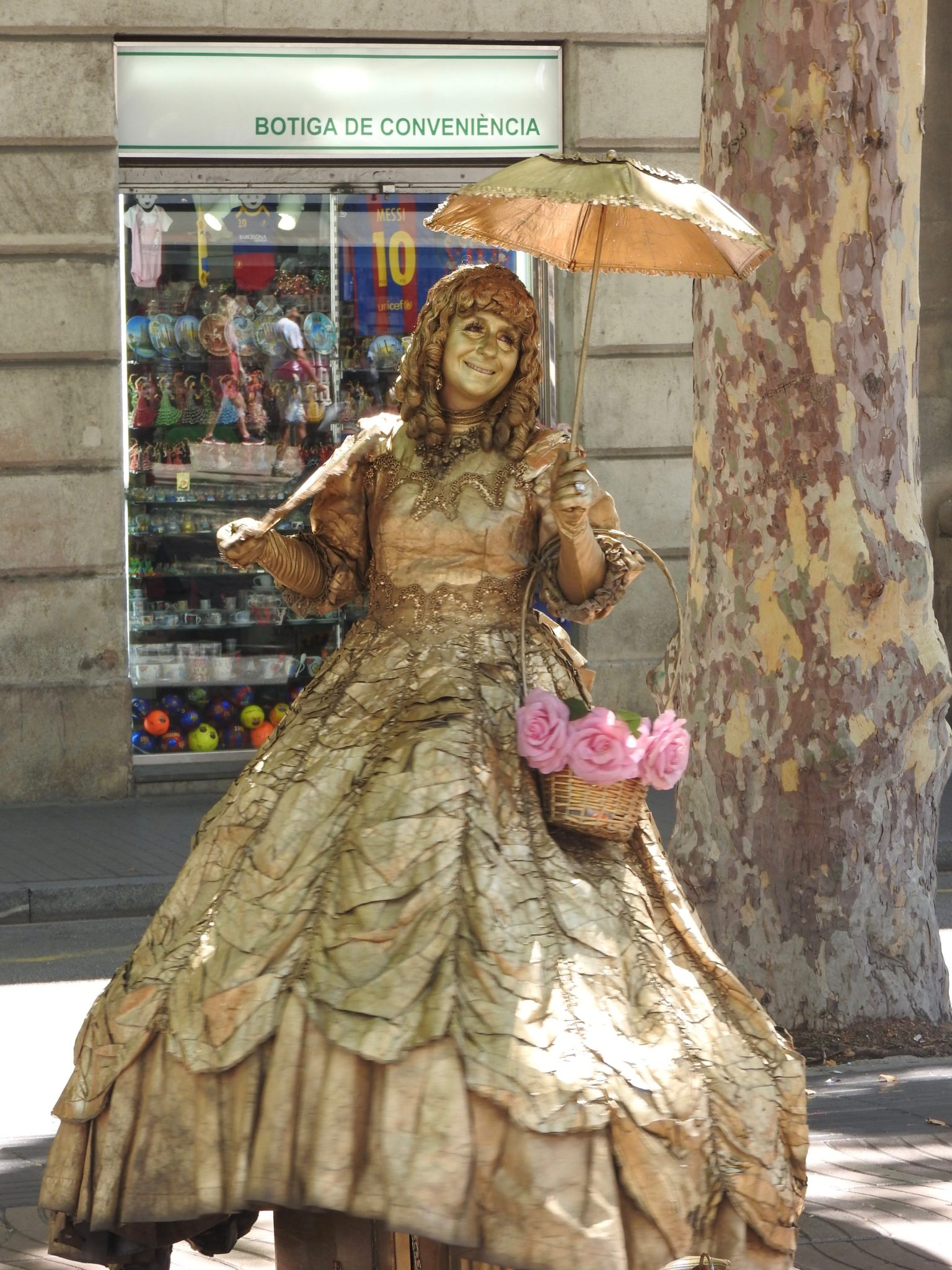 Street performer in gold make up and hoop skirt